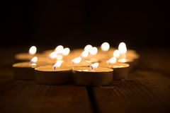 Several candles burning in the dark Royalty Free Stock Images