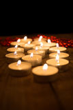 Several candles burning in the dark Stock Photo
