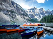 SEVERAL CANOES ON A DOCK ON LAKE MORAINE WITH MOUNTAIN BACKGROUND Royalty Free Stock Photography