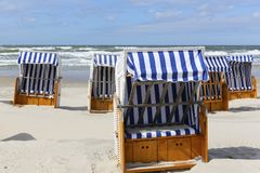 Several canopied beach chairs by a sea coast. View of several canopied beach chairs that can be seen at the beach in Kolobrzeg by the Baltic sea coast Royalty Free Stock Photography