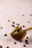 Several capers in wooden spoon on white board Royalty Free Stock Photos