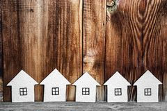 Several cardboard houses on a wooden background. Stock Photo