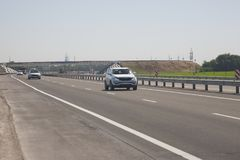 Several cars are driving along the highway. In the background, the bridge royalty free stock image