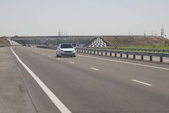 Several cars are driving along the highway. In the background, the bridge stock photos
