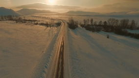 Several cars driving on icy road at the dusk to the mountains. Several cars driving on icy road at the dusk. Aerial footage stock video