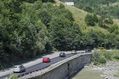 Several cars driving on a mountain road. Photos of summer holidays in the mountains stock image