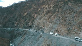 Several cars traveling on a mountain road in the mountains. A trip to the mountains stock footage
