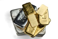 Several cast and minted gold bars and silver cast bars isolated on white background. stock photo