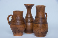 Several ceramic jug. Several brown ceramic jug on a gray background Stock Images