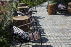 Several chairs with cushions and wooden logs as tables Royalty Free Stock Photography