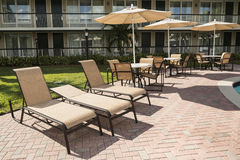 Several chairs with a parasol for sunbathing by the pool. Florid Stock Images