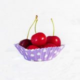 Several cherries inside a cupcake liner Royalty Free Stock Images