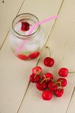 Several cherries next two fruit drink in a jar with straw Stock Photography