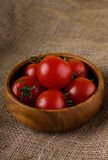Several cherry tomatoes in a bowl on jute cloth Royalty Free Stock Image