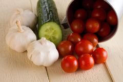 Several cherry tomatoes and garlic with cucumber on white board Royalty Free Stock Photos