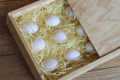 Several chicken white eggs in a wooden box. Several chicken white eggs in a wooden box on a soft substrate. Reliable and safe packing. Unusual angle Royalty Free Stock Photos