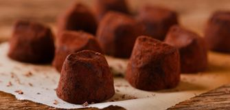 Several chocolate truffles on piece of paper Stock Images