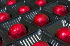 Several chocolates in red foil Royalty Free Stock Photos