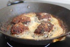 Several chops boiling oil on old frying pan. Several chops with roasted golden brown in boiling oil on old frying pan Stock Photo
