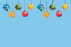Several Christmas multi-colored balls painted with watercolors hanging on threads on a blue background Royalty Free Stock Photography