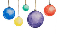 Several Christmas multi-colored balls painted with watercolors hanging on threads on a white background Stock Photos