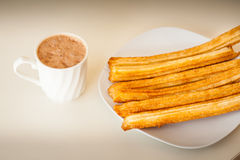 Several churros on small plate and milk with chocolate Stock Images
