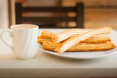 Several churros on small plate and milk with chocolate Stock Image