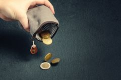 Several coins fall on the table from an empty wallet in a woman`s hand, poverty, crisis, bankruptcy and financial problems concep stock photo