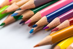 Several color pencils on a white paper sheet Stock Photos