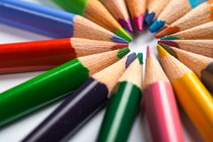 Several color pencils on a white paper sheet Royalty Free Stock Photography