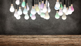 Several colored light bulbs in front of a blackboard. 3D Rendering Stock Photography