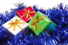 Several colorful Christmas presents on garland. Several colorful Christmas presents resting on blue garland stock images