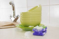 Several colorful plates, kitchen sponges. Royalty Free Stock Photos