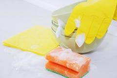 Several colorful plates, kitchen sponges. Stock Photos