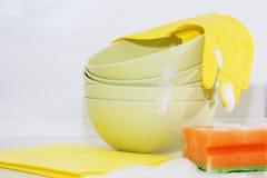 Several colorful plates, kitchen sponges. Stock Images