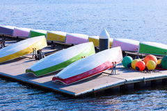 Several colourful small sailing boats demounted and overturned drying on a floating platform Royalty Free Stock Photography