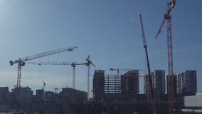 Several construction cranes against a clear blue sky background stock video footage