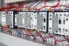 Several contactors arranged in a row in an electrical closet. The contactors connected wire number coded. Contactors with front auxiliary contacts. The wires Royalty Free Stock Photos