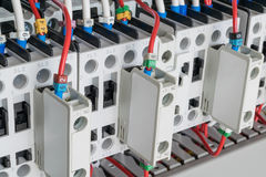 Several contactors arranged in a row in an electrical closet. The contactors connected wire number coded. Contactors with front auxiliary contacts. The wires Stock Photos