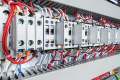 Several contactors arranged in a row in an electrical closet. The contactors connected wire number coded. Contactors with front auxiliary contacts. The wires stock images