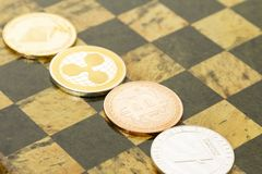 Several cryptocurrencies, bitcoin, ethereum, litecoin, ripple on chessboard. Nice shiny Several cryptocurrencies, bitcoin, ethereum, litecoin, ripple on royalty free stock image