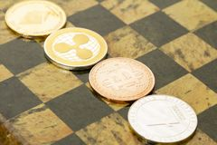 Several cryptocurrencies, bitcoin, ethereum, litecoin, ripple on chessboard. Nice shiny Several cryptocurrencies, bitcoin, ethereum, litecoin, ripple on royalty free stock photo