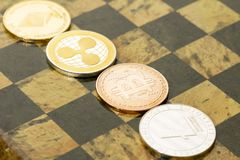 Several cryptocurrencies, bitcoin, ethereum, litecoin, ripple on chessboard. Nice shiny Several cryptocurrencies, bitcoin, ethereum, litecoin, ripple on royalty free stock photography