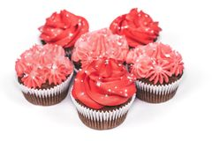 Several cupcakes with red and pink icing on isolated white background. royalty free stock photo