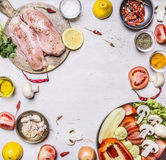 Several delicious raw turkey breast On a cutting board with seasoning a variety of fruits vegetables laid frame rustic Royalty Free Stock Image