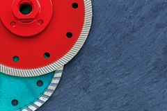 Several diamond cutting wheels of red and emerald color against a background of gray granite. stock image