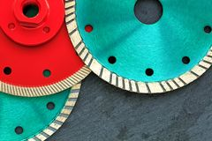 Several diamond cutting wheels of red and emerald color against a background of gray granite stock images