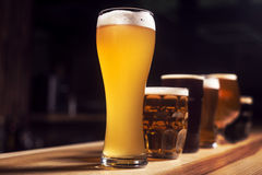 Several different beers are standing in a row. At the bar Stock Photography
