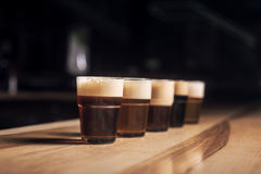 Several different beers are standing in a row. At the bar in small mugs Royalty Free Stock Images