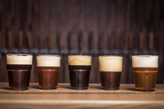 Several different beers are standing in a row. At the bar in small mugs Stock Photos